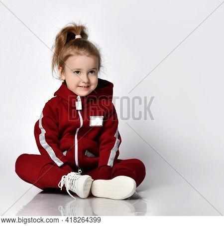 Cute Little Preschooler Girl Wearing Warm Tracksuit Sportswear With Hood And White Sneakers Sitting