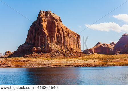Grandiose cliffs. The Colorado River, USA. Tour on a pleasure boat on an artificial reservoir Lake Powell. Grandiose cliffs - red sandstone outcroppings. Concept of active and photo tourism
