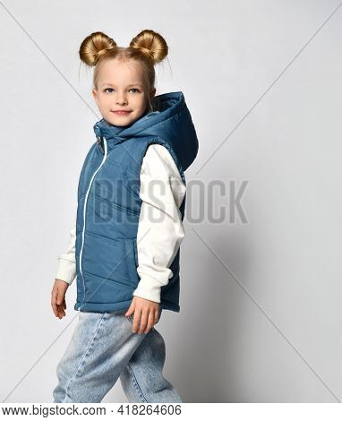 Side View Of A Little Girl In Warm Outerwear Blue Sleeveless Vest, Jeans And A Sweatshirt, Posing Fo