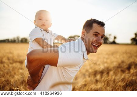 Happy Dad And Son In A Wheat Field. A Man Holds A Little Boy In His Arms. Summer Photo With The Baby