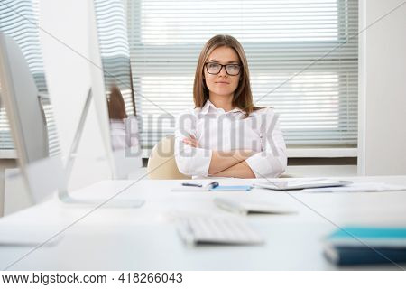 Portrait of pretty business woman looking at camera at workplace in an office