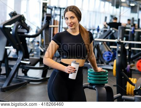 Beautiful Athletic Woman In The Sportswear Does A Fitness Workout In The Gym. Athlete Enjoys Her Tra