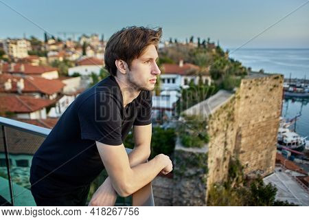 Slender European Man, About 20 Years Old, Sadly Looks At Old City In Antalya From Observation Point.