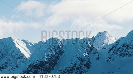 Winter Landscape With Snow Covered Mountains. Beautiful Cloudy Sky In The Background. High Quality P