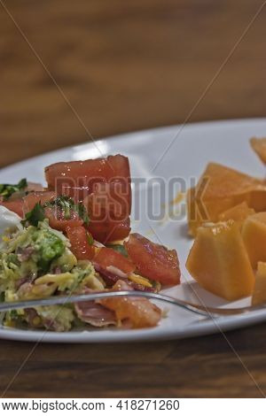 White Plate With Cantaloupe And Mediterranean Salad