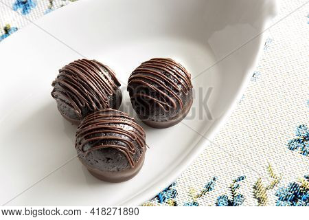 Chocolate Candy Truffles In White Plate. Homemade Dark Chocolate Truffles. Delicious Chocolate Desse