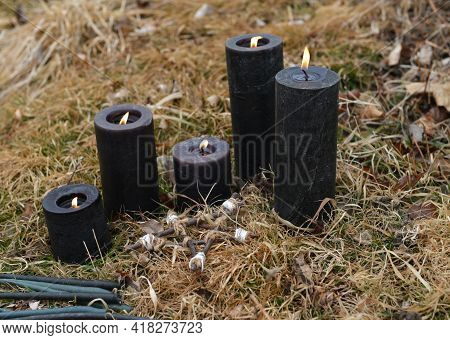 Magic Ritual With Burning Black Candles In The Grass.  Esoteric, Gothic And Occult Background, Hallo