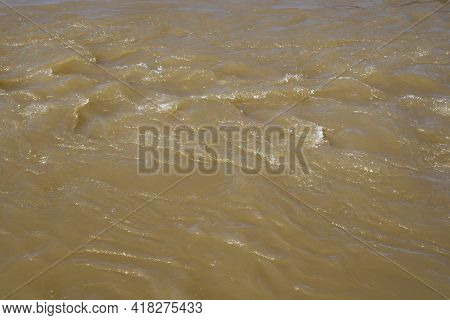 Turbid Stream Of Water. Spring River With Brown Muddy Water. Close-up.