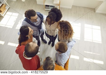 View From Above Of Happy Diverse Business Partners And Coworkers Huddling In Office