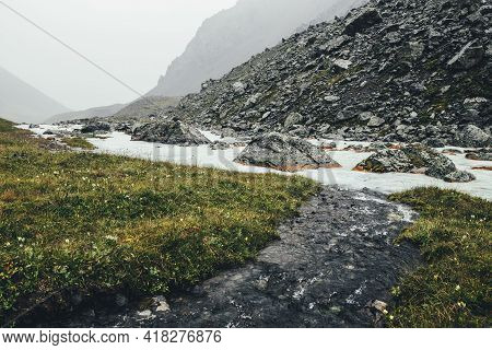 Atmospheric Landscape With Clear Water Stream Flows Into Mountain River Among Moraines In Rainy Weat