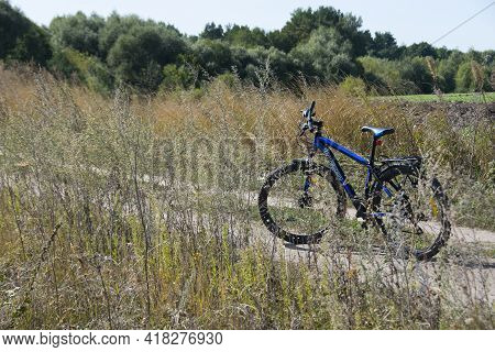 Bike Stands On In The Field. A Mountain Bike Stands On A Field Path With Dry Grass. Cycling. Mountai
