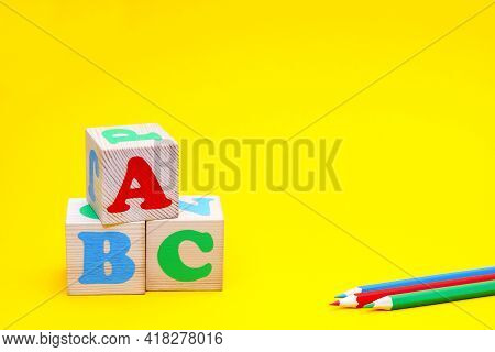 Abc -the First Letters Of The English Alphabet On Wooden Toy Cubes On A Yellow Background Next To Co
