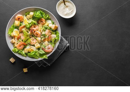 Shrimp Salad. Seafood Caesar Salad Served With Croutons,caesar Sauce And Parmesan On Black Backgroun