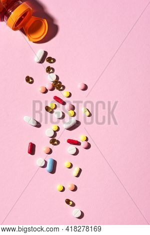 Multicolored Tablets, Pills, Capsules Falling From Plastic Bottle On Pink Background. Heap Of Assort