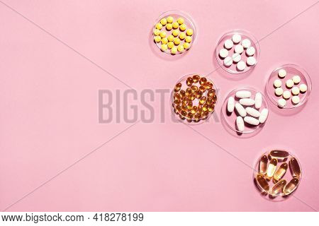 Vitamins Capsules On Pink Background, Top View, Copy Space. Food Supplements: Fish Oil, Omega 3, Ome