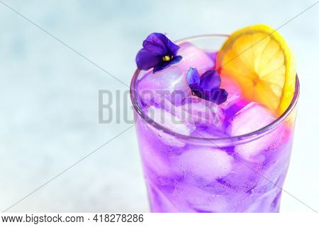 Purple Haze Cocktail With Lemon And Violet Bloom, Close Up. Violet Soda Drink With Ice Cubes.