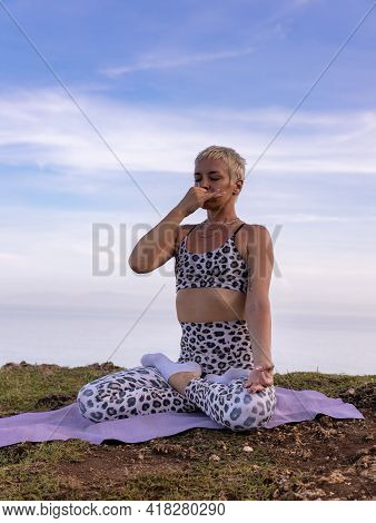 Yogi Woman Sitting In Lotus Pose, Practicing Anuloma Viloma Pranayama, Alternate Nostril Breathing.