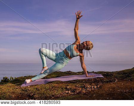 Sunrise Yoga. Slim Woman Practicing Utthita Vasisthasana. Side Plank Pose Knee Variation. Strong Fit
