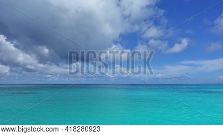Calm Waters Of The Aquamarine Indian Ocean. There Are Picturesque Cumulus Clouds In The Azure Sky. N