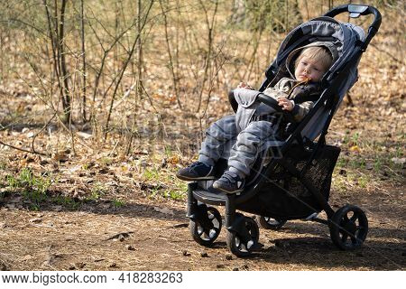 Tired Boy With Blond Hair Is Resting Sitting In A Baby Carriage. A One-year-old Boy Walked Through A