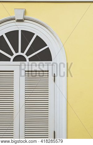 Part Of Vintage White Wooden Arch Window On Yellow Cement Wall Background In Vertical Frame