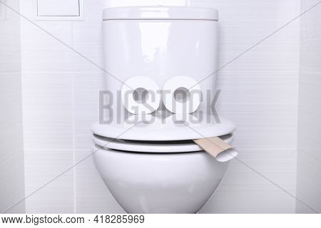White Home Toilet With Flush And White Toilet Paper In The Bathroom.