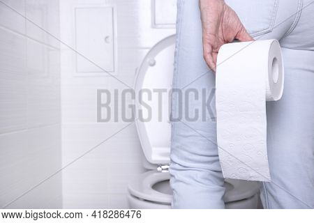 Pissing Woman Suffering From Diarrhea In A White Toilet, In A Toilet With A Roll Of White Paper With