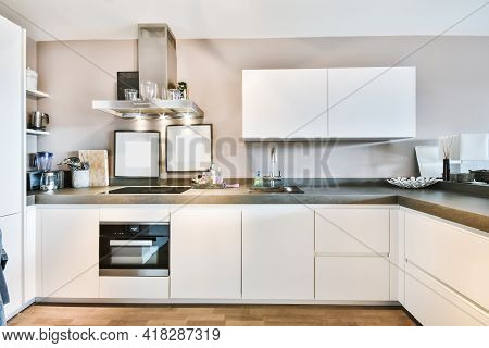 Interior Of Minimalist Style Kitchen With Simple Cupboards And Modern Appliances In Light Apartment