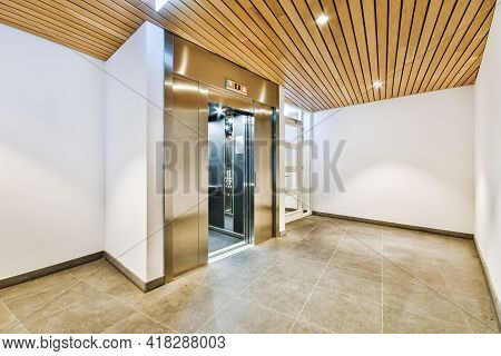 Shiny Elevator With Opened Door Located In Illuminated Hall Of Contemporary Apartment Building With