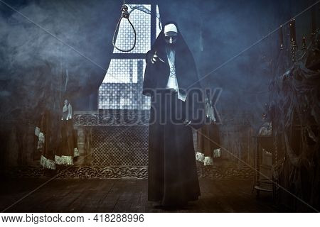 Full length portrait of a scary cursed nun standing in the abandoned chapel with a loop for hanging. Horrors. Halloween.