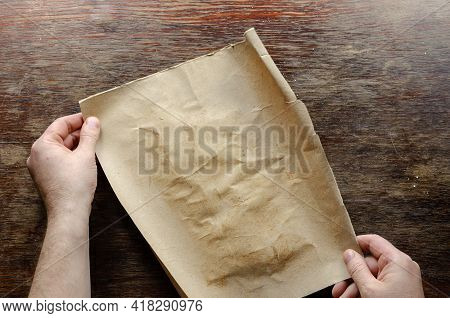 Brown Sheet Of Paper And Hands On A Wooden Table. A Man Holds A Piece Of Torn Brown Paper On A Scrat