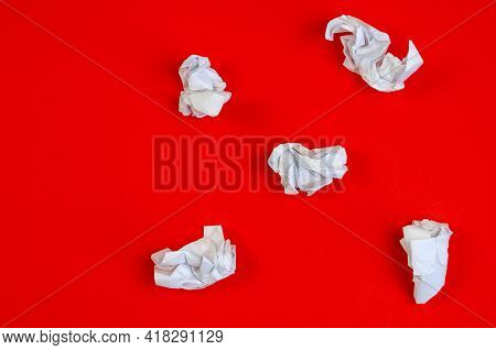 Crumpled Scraps Of White Paper On A Red Background. Five Pieces Of Crumpled Paper Lying Chaotically.