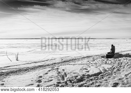 A Man Is Sitting On A Beach On A Winter Day. The Bothnian Bay Is Frozen Deep And There Is Quite A Lo