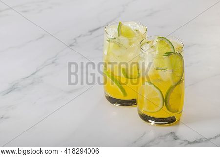 Two Glasses Of Refreshing Lemon, Lime And Ice Cocktail. Close-up, Copy Space, Marble Backdrop.