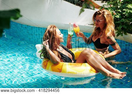 Attractive Smiling Young Women Enjoying Pool Party, Talking And Drinking Cocktails