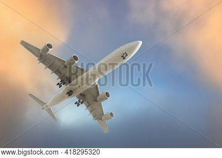 Air plane flying between clouds in sunset sky, closeup.