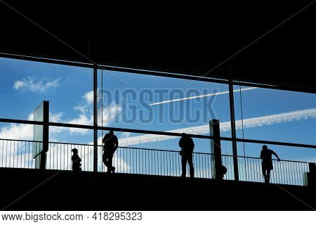 People silhouettes in large airport structure over white sky background.