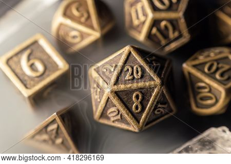 Close-up Image Of A Set Of Copper Role Playing Dice Surrounded By Smoke.
