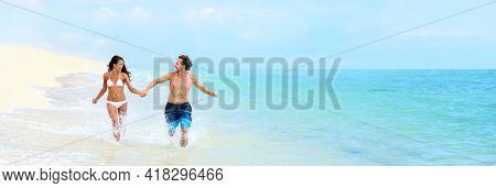 Beach couple Caribbean vacation summer travel fun splashing water running in fit bikini body. Happy tourists relaxing laughing enjoying paradise holiday banner panoramic.