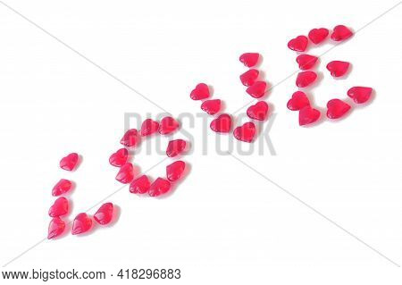Glass Pink Hearts Laid Out In Word Love. Diagonal, White Isolated Background.