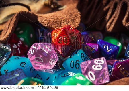 Close-up Image Of A Red Marbled 20-sided Die On A Pile Of Various Colored And Shaped Dice Spilling O