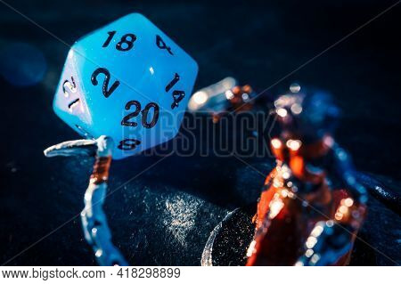 Close-up Of A Blue Twenty Sided Dice And A Role Playing Mini On A Dark Surface. Focused On The Dice