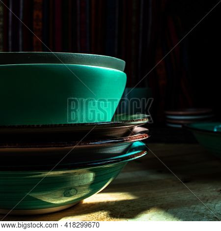 Close Up Of Dishware Stacked Up In The Dark
