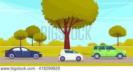 Cars Drive On An Asphalt Road In Countryside Against Green Forest With Large Trees. Country Road And