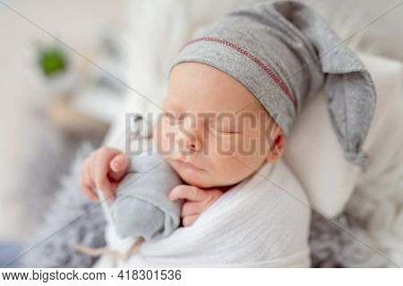 Closeup portrait of infant newborn baby boy sleeping and hugging mouse toy