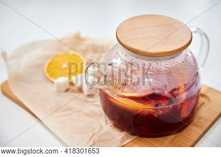 Berry Tea With Orange In A Transparent Teapot On Light Background. Close-up, Selective Focus
