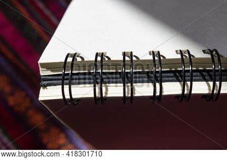 Sketchbook Placed With The Spiral Binding Up Partly In The Shade On Colorful Surface