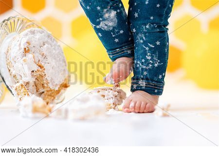 Birthday. A Small Child's Feet Smeared In Cream, And A Cake Lying On The Floor In Close-up. In The B