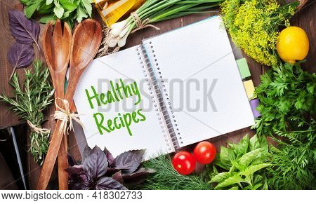 Fresh garden herbs and cookbook for your healthy recipes on wooden table. Top view flat lay