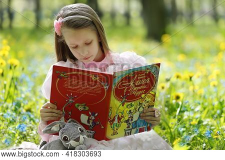 Belarus, The City Of Gomil, 06 05 2016 Central Park. A Beautiful Girl Reads The Book Alice In Wonder